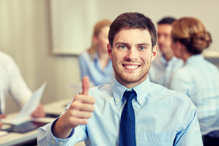 colleagues: business, people, gesture and teamwork concept - smiling businessman showing thumbs up with group of businesspeople meeting in office