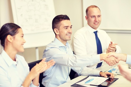 shaking: business, people and partnership concept - smiling business team shaking hands and applauding in office