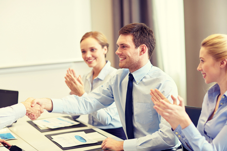 deal: business, people and partnership concept - smiling business team shaking hands and applauding in office