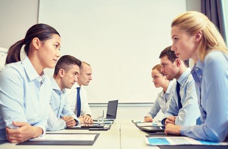 비즈니스, 사람, 위기와 대립 개념 - 사무실에서 반대편에 앉아 비즈니스 팀 웃는
