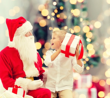 holidays, childhood and people concept - smiling little boy with santa claus and gifts over christmas tree lights background