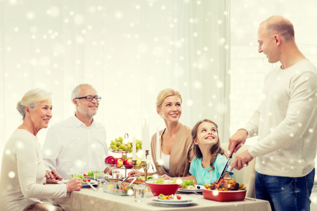 family indoors: family, holidays, generation, christmas and people concept - smiling family having dinner at home