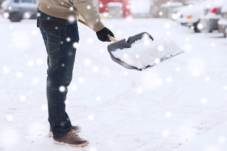 removing: transportation, winter, people and vehicle concept - closeup of man digging snow with shovel near car