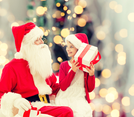 preteen girl: holidays, childhood and people concept - smiling little girl with santa claus and gifts over christmas tree lights lights background