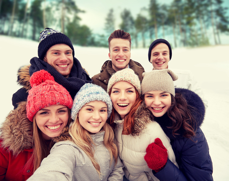 in nice: winter, technology, friendship and people concept - group of smiling men and women taking selfie outdoors