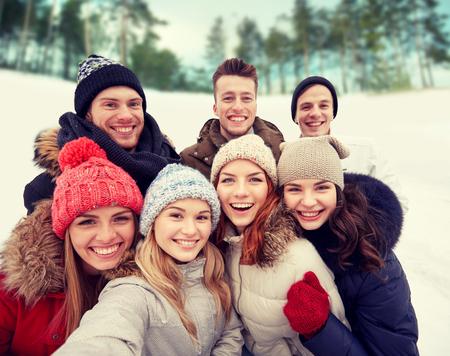 zimě, technologie, přátelství a lidé koncepce - skupina usmívající se mužů a žen užívajících selfie venku