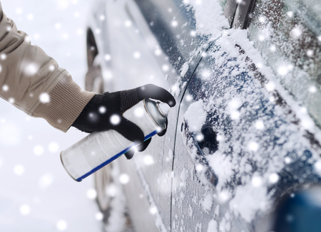 frost winter: transportation, winter, people and vehicle concept - closeup of man hand with lock door de-icer Stock Photo