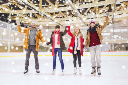 iceskates: people, friendship, gesture, sport and leisure concept - happy friends waving hands on skating rink