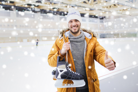 iceskates: people, sport, gesture and leisure concept - happy young man with ice-skates showing thumbs up on skating rink Stock Photo