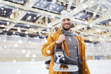 iceskates: people, sport and leisure concept - happy young man with ice-skates on skating rink