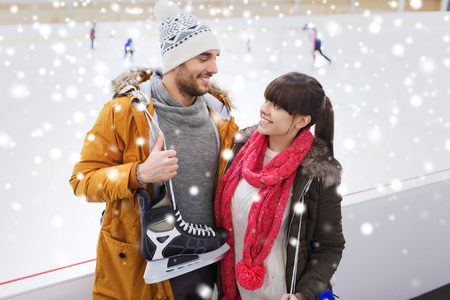 family activities: people, friendship, sport and leisure concept - happy couple with ice-skates on skating rink
