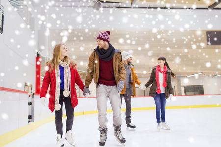 boy skating: people, friendship, sport and leisure concept - happy friends on skating rink