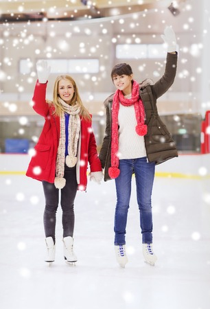 women friendship: people, women, friendship, sport and leisure concept - two happy girls friends waving hands on skating rink Stock Photo