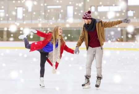 Les gens, l'amitié, le sport et le concept de loisirs - heureux couple se tenant les mains sur la patinoire Banque d'images - 48023700