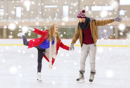 ice arena: people, friendship, sport and leisure concept - happy couple holding hands on skating rink