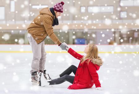 patinaje sobre hielo: la gente, la amistad, el deporte y el ocio concepto - hombre sonriente ayudar a las mujeres se levanten en la pista de patinaje
