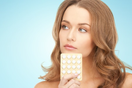 birth control pill: beauty, people, medicine and health care concept - beautiful young woman with medication over blue background