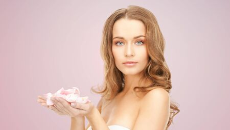 beauty woman: beauty, people and health concept - beautiful smiling young woman with flower petals and bare shoulders over pink background