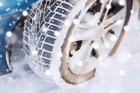 tire tracks: transportation, winter and vehicle concept - closeup of car wheel Stock Photo