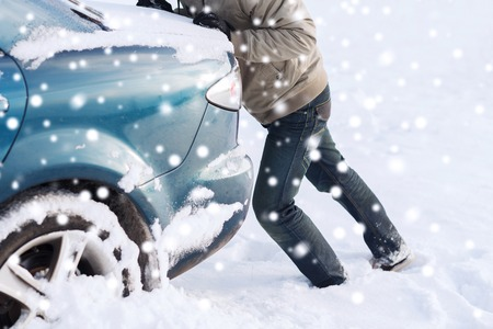 transportation, winter, people and vehicle concept - closeup of man pushing car stuck in snow Stock Photo
