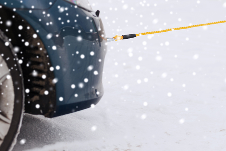 towed: transportation, winter and vehicle concept - closeup of towed car with towing rope
