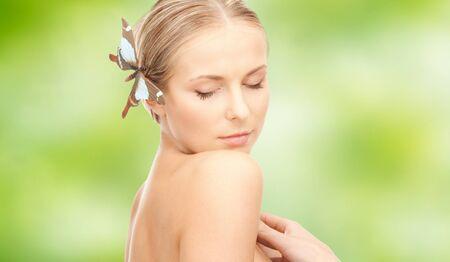donna farfalla: gente, la bellezza, il corpo e il concetto di cura della pelle - giovane e bella donna felice con la farfalla della forcella su sfondo verde naturale