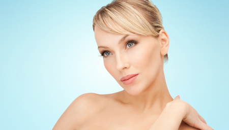 smile face: beauty, people and health concept - beautiful young woman with bare shoulders over blue background