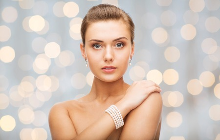 bride bangle: beauty, luxury, people, holidays and jewelry concept - beautiful woman with pearl earrings and bracelet over lights background