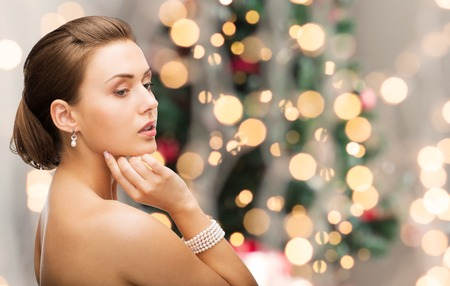 bijouterie: beauty, luxury, people, holidays and jewelry concept - beautiful woman with pearl earrings and bracelet over christmas lights background Stock Photo