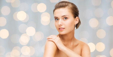 beauty, luxury, people, holidays and jewelry concept - beautiful woman with diamond earrings over lights background Stock Photo