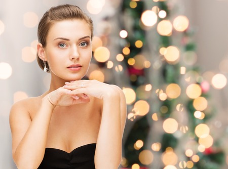 fashion jewelry: beauty, luxury, people, holidays and jewelry concept - beautiful woman with diamond earrings over christmas lights background