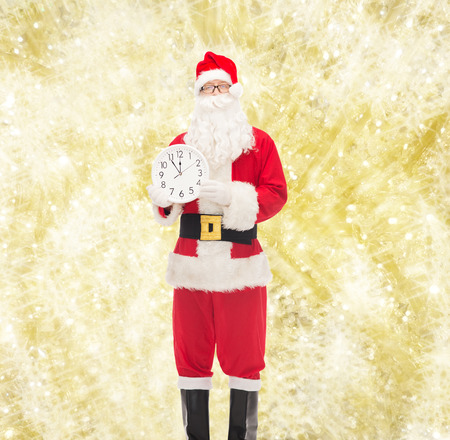 12 oclock: christmas, holidays and people concept - man in costume of santa claus with clock showing twelve over yellow lights background