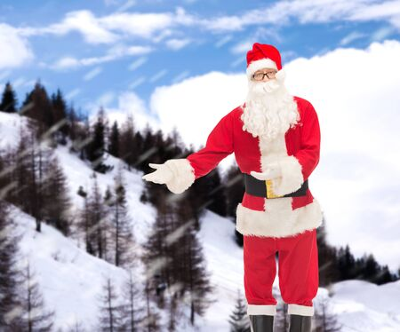 christmas costume: christmas, holidays, gesture and people concept - man in costume of santa claus over snowy mountains background Stock Photo