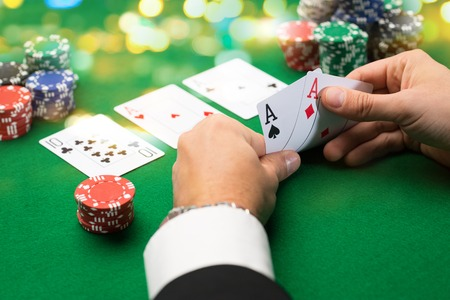 casino, gambling, poker, people and entertainment concept - close up of poker player with playing cards and chips at green casino table over holidays lights background 스톡 콘텐츠