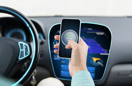 automotive: transport, business trip, technology and people concept - close up of male hands with start engine button on smart phone screen in car Stock Photo