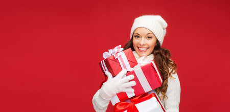 pretty lady: christmas, x-mas, winter, happiness concept - smiling woman in sweater and hat with many gift boxes