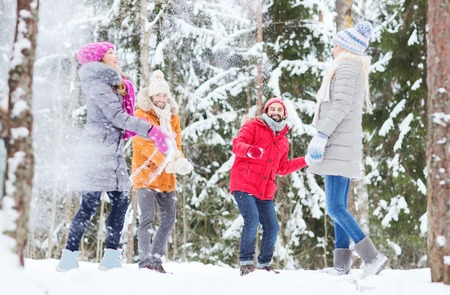 snowballs: love, season, friendship, entertainment and people concept - group of happy men and women having fun and playing snowballs in winter forest