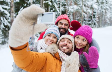 gente saludando: la tecnolog�a, la estaci�n, la amistad y el concepto de la gente - grupo de sonrientes hombres y las mujeres que toman Autofoto con c�mara digital en el bosque de invierno
