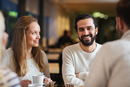 communication: people, leisure, communication, eating and drinking concept - happy friends meeting and drinking tea or coffee at cafe