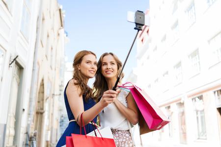 ショッピング バッグ スマート フォン selfie で写真を撮ると幸せな若い女性にこだわる街販売、技術、友情、人のコンセプト- 写真素材