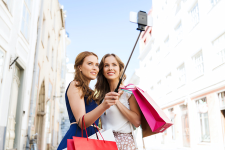 sale, technology, friendship and people concept - happy young women with shopping bags taking picture by smartphone selfie stick on city street