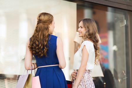 mujeres de espalda: la venta, el consumo y el concepto de las personas - mujeres jóvenes felices con bolsas de la compra hablando en el escaparate de la ciudad en la parte posterior