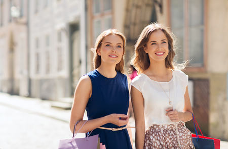 2 persons: sale, consumerism and people concept - happy young women with shopping bags walking along city street