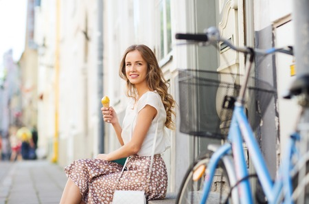 ice cream woman: people, style, technology, leisure and lifestyle - happy young hipster woman with fixed gear bike eating ice cream on city street