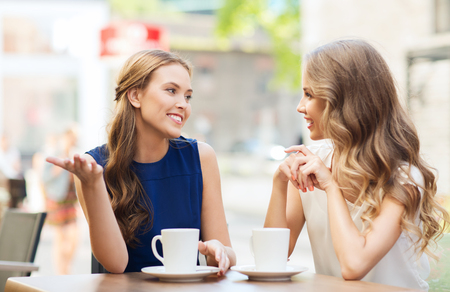 amigos hablando: personas, la comunicación y el concepto de la amistad - sonriendo mujeres jóvenes beber café o té y que hablan en el café al aire libre