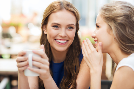 people communication and friendship concept - smiling young women drinking coffee or tea and gossiping at outdoor cafe Standard-Bild