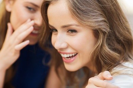 people, communication and friendship concept - smiling young women gossiping and whispering secrets Standard-Bild