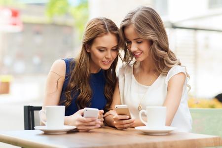 技術、ライフ スタイル、友情、人コンセプト - 幸せな若い女性やスマート フォンと屋外カフェでコーヒー カップで 10 代の少女 写真素材