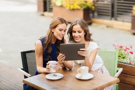lifestyle: tecnología, estilo de vida, la amistad y el concepto de la gente - mujeres jóvenes felices o adolescentes con tablet pc beber café ordenador en café al aire libre