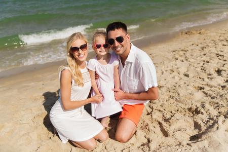 uomo felice: famiglia, le vacanze, l'adozione e la gente di concetto - uomo felice, donna e bambina in occhiali da sole sulla spiaggia d'estate